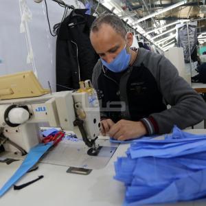 عمال بغزة يحيكون أقنعة وملابس طبية