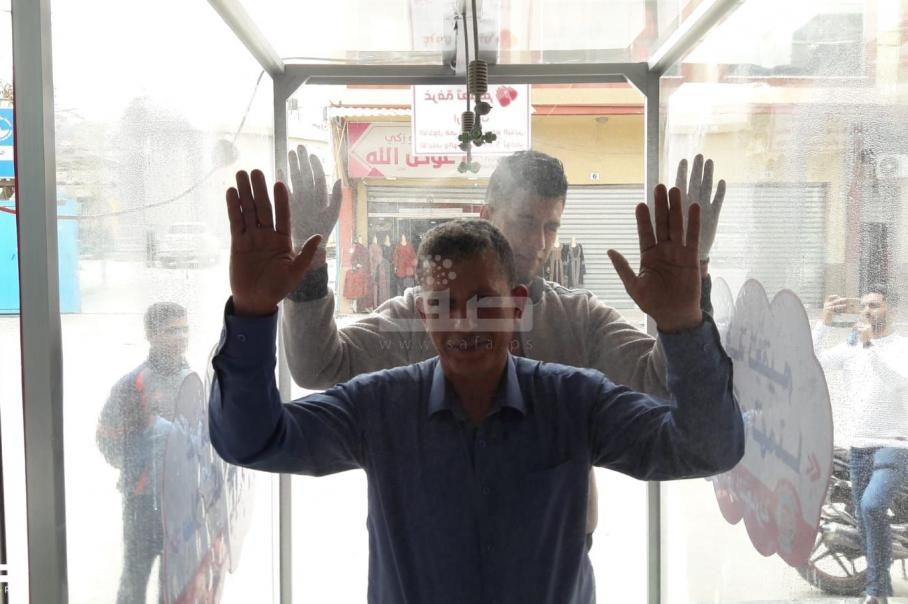 مؤسسة تجارية في غزة تقيم غرفة تعقيم للزبائن