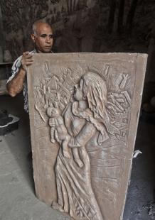 فنان بارع في نحت الجداريات الفخارية بغزة