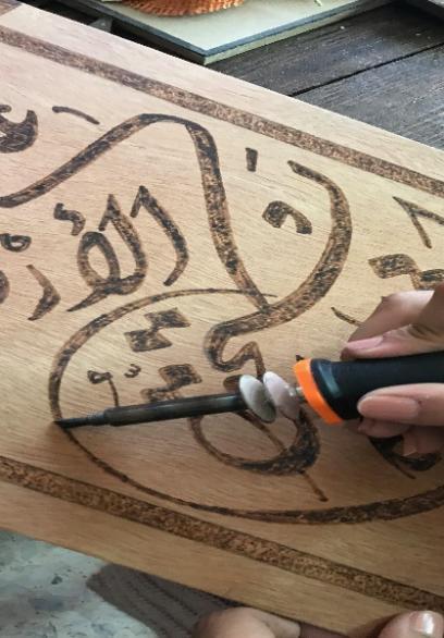 فنانة من رفح تنقش على الخشب