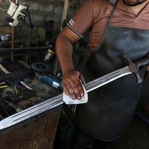 شاب يصنع السيوف والخناجر في ورشته بخان يونس