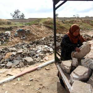 مواطنة بخان يونس تجمع الحجارة لبيعها
